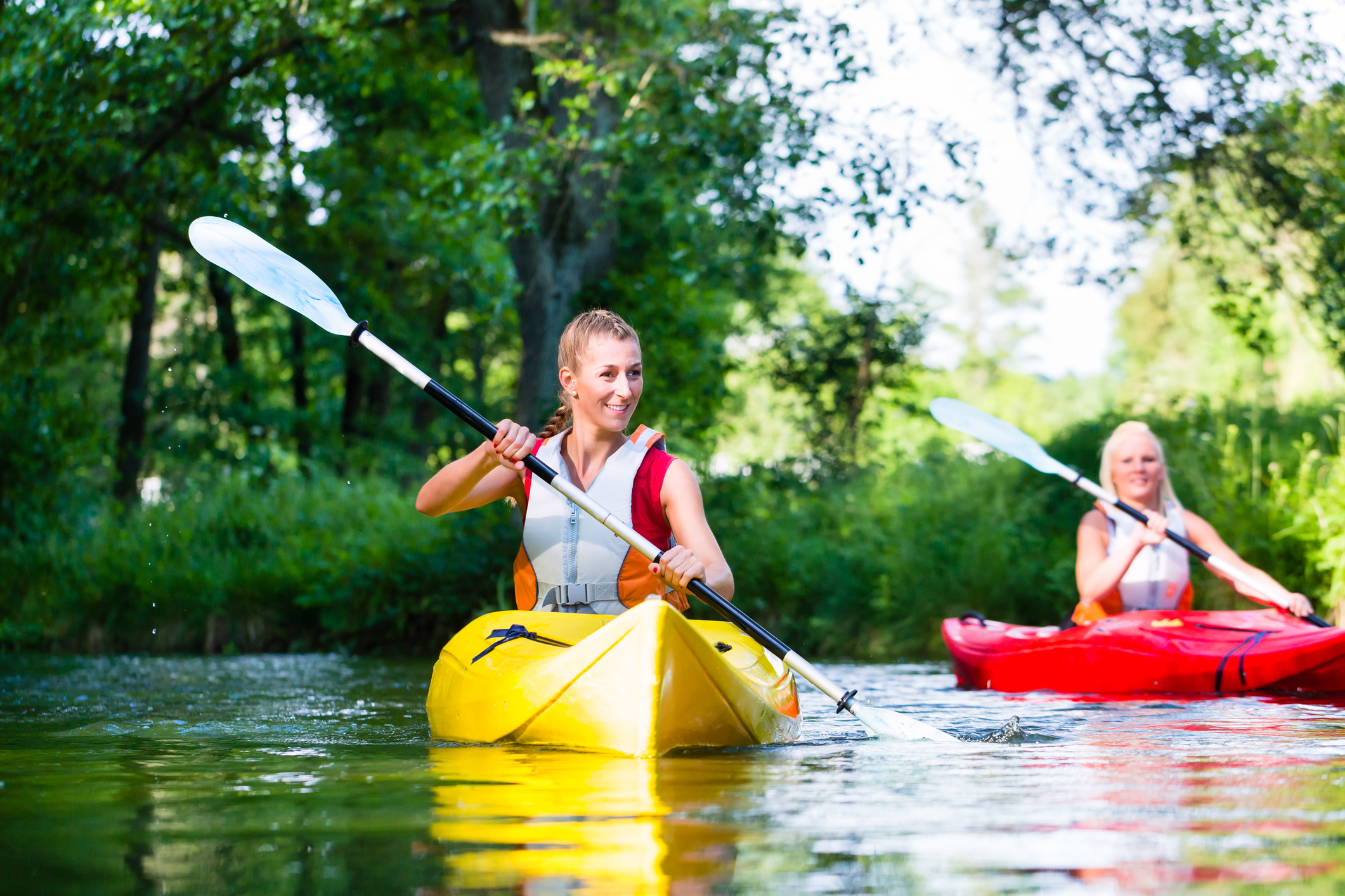 two friends kayaking in a river surrounded by forest.