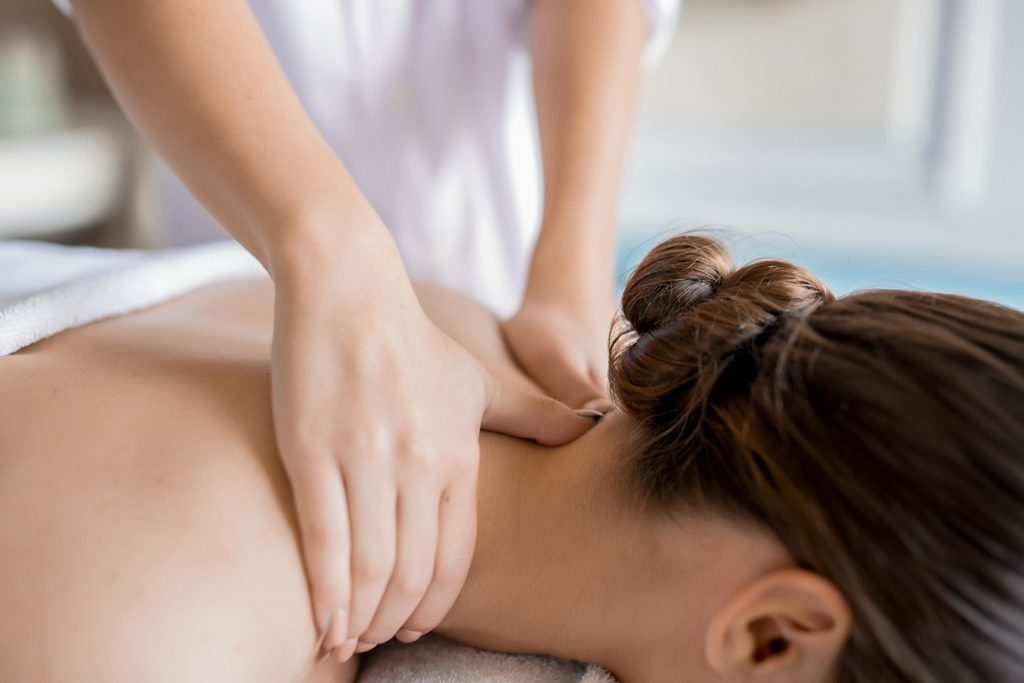 Hands of masseuse massaging neck and shoulders of relaxed client